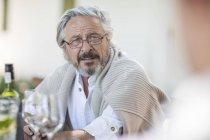 Старший мужчина обедает с вином — стоковое фото