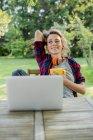 Junge Frau entspannende Tasse mit Laptop am Gartentisch — Stockfoto
