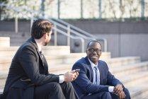 Dois empresários sorridentes, sentado na escada e falando — Fotografia de Stock