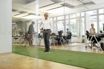 Businessman playing golf in modern office — Stock Photo