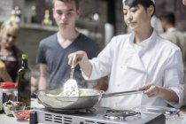 Chef instructor stirrs pot with male teen in cooking class — Stock Photo