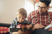 Vater und Sohn spielen Spielzeug-Musikinstrumente — Stockfoto