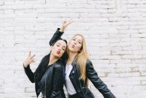 Two young women pouting mouth and showing victory sign in front of white brick wall — Stock Photo