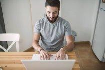 Jeune homme à l'aide d'ordinateur portable à la maison — Photo de stock