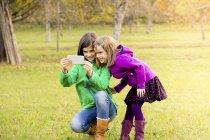 Дві усміхнений сестри прийняття selfie з мобільний телефон на луг восени — стокове фото