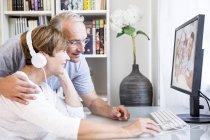 Старшая пара за столом с компьютером, женщина в наушниках — стоковое фото