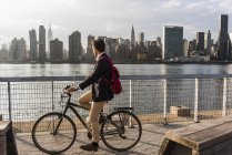 Uomo d'affari in bicicletta e guardando skyline di Manhattan, New York, Stati Uniti — Foto stock