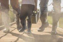 Dois homens e garotinho vestindo botas andando sobre a ponte com caixa — Fotografia de Stock