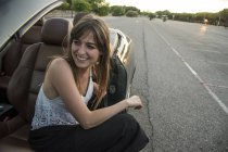 Smiling young woman sitting in convertible — Stock Photo