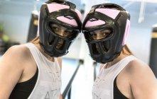 Mujer joven con protector de cabeza en el gimnasio - foto de stock