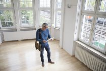 Man looking at document in empty apartment — Stock Photo