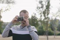 Мужчина фотографирует на винтажную камеру — стоковое фото