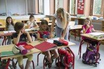 Учитель помогает школьница в классе в школе — стоковое фото