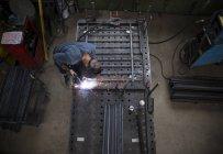 Man welding railing of metal construction — Stock Photo