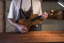 Luthier holding a violin in his workshop — Stock Photo