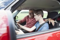 Father teaching son driving car — Stock Photo