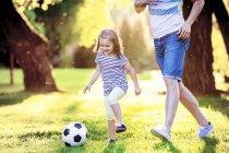 Bambina felice giocando a calcio con suo padre in un parco — Foto stock