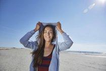Sorridente giovane donna che indossa felpa con cappuccio sulla spiaggia — Foto stock