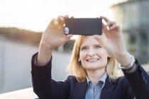 Empresaria tomando selfie con smartphone - foto de stock
