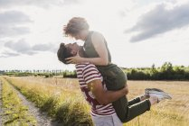 Man lifting up girlfriend on field path — Stock Photo