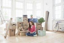 Femme entourée de boîtes en carton utilisant une tablette numérique — Photo de stock