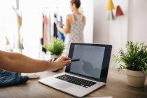 Hombre apuntando a la computadora portátil con la mujer en el fondo - foto de stock