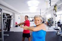 Mature woman and senior man doing gymnastics — Stock Photo