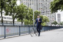 Businessman with bicycle walking in the city and using smartphone — Stock Photo