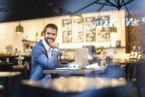 Sonriente hombre de negocios con ordenador portátil trabajando en café - foto de stock