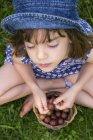 Девушка сидит на лугу с корзиной крыжовника — стоковое фото