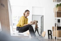 Smiling woman sitting on office desk using digital tablet — Stock Photo