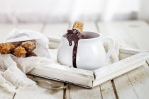 Churros bisquits with hot chocolate in jug on wooden tray — Stock Photo