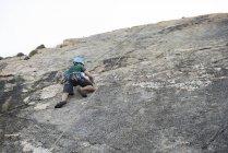 Giovane arrampicata su una parete di roccia — Foto stock