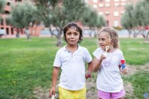 Little girl and boy with bubble rings in a park — Stock Photo