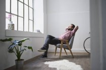 Man sitting in chair and daydreaming in modern building — Stock Photo