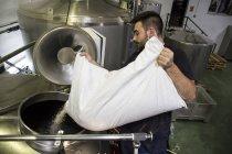 Man gießt einen Beutel mit Malz in einem Bier-Tank in einer Fabrik — Stockfoto