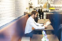 Geschäftsmann im Café sitzen und Zeitung lesen — Stockfoto