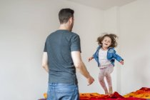 Father looking at daughter bouncing on bed — Stock Photo