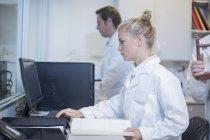 Jeune femme travaillant sur ordinateur en laboratoire — Photo de stock
