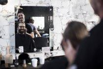 Парикмахерские и заказчика, отражения в зеркале — стоковое фото