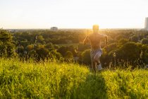 Man running on meadow in park at sunset — Stock Photo