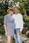 Casal feliz com mulher grávida de pé no jardim — Fotografia de Stock