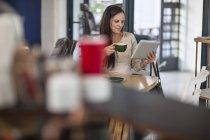 Madura mujer caucásica con tableta en un café - foto de stock