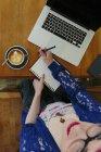 Mujer joven con portátil y portátil sentado en una cafetería, vista superior - foto de stock