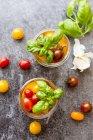 Fermentierte Tomaten im Einmachglas auf grauer Tischplatte mit Basilikumblättern — Stockfoto