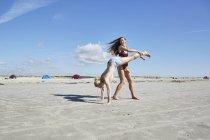 Jeune femme aidant un ami faisant le poirier sur la plage — Photo de stock