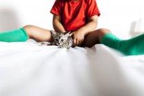 Cortada a imagem do menino sentado na cama segurando gatinho — Fotografia de Stock