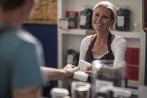 Frau im Café übergibt Quittung an Kundin — Stockfoto
