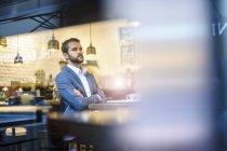 Серйозний бізнесмен, сидячи в кафе з обіймами перетнула — стокове фото