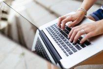 Las manos de la mujer que escribe en el teclado del portátil - foto de stock